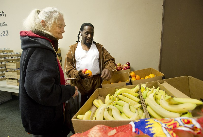 Erie resident Billie McCafferty. 68, left, selects fresh produce with the help of Al-Mujahideen Sirrajuldeen Siffullah Muhammad Ibin Henrun, 48, who is an Erie City Mission Family Care Center volunteer working at the center in Erie on Nov. 13. McCafferty said she comes to the food pantry each week. ANDY COLWELL/