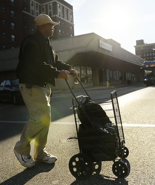 Erie resident David Austin, 58, crosses Peach Street with food he received from the Erie City Mission's Family Care Center on Nov. 11. Austin said he and his fiancée make do with the $1054 he receives per month from his U.S. Army pension but turn to the food pantry to supplement the pension.  ANDY COLWELL/