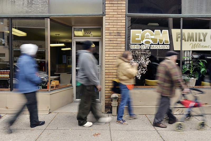 Part of a 40-person line files into the Erie City Mission's Family Care Center food pantry as it opens on Nov. 6. A September 2014 report released by the Second Harvest Food Bank of Northwest Pennsylvania has shown that one in three people in Erie County turn to food pantries, soup kitchens and other meal-service programs like the Erie City Mission's. Some of those in line said they had been waiting since at least 6:30 that morning.  ANDY COLWELL/