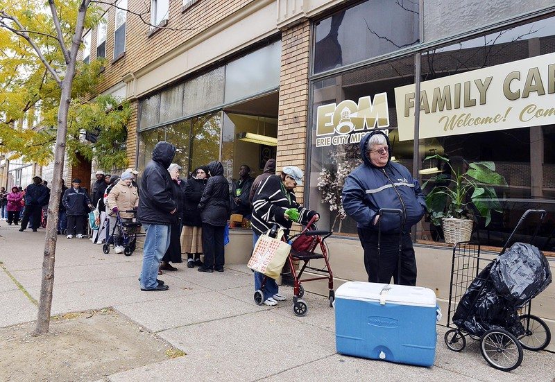 Erie resident Denny Plonski, 68, stands with his cooler while waiting in a line of about 40 people for the Erie City Mission's Family Care Center food pantry to open at 9 a.m. on Nov. 6. A September 2014 report released by the Second Harvest Food Bank of Northwest Pennsylvania has shown that one in three people in Erie County turn to food pantries, soup kitchens and other meal-service programs like the Erie City Mission's. Plonski said he and others ahead of him had been in the line since at least 6:30 that morning.  ANDY COLWELL/