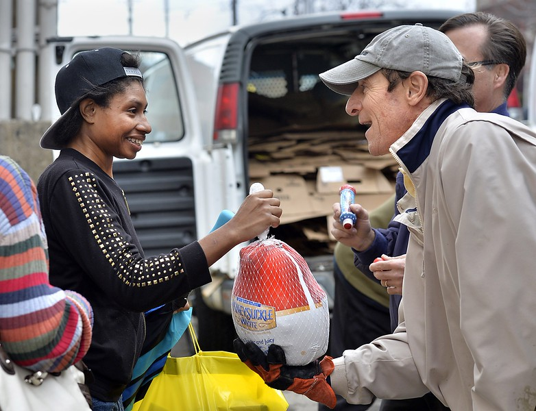 "Erie resident Akisha Winslow, 37, left, smiles as she receives a frozen turkey from Erie City Mission volunteers Doug Nelson, 59, front right, and Greg Paulding, 58, back right, both of Millcreek Township, at the mission's annual Thanksgiving Basket Distribution on Nov. 24. ""We're prepared to serve over 1,300 (people),"" said Rick Crocker, executive director of the Erie City Mission, ""and I expect that we'll be able to serve everyone waiting in line."" Hundreds waited in lines that stretched in front of the mission on French Street and down both East 11th and East 10th streets. Warm temperatures in the 60s contributed to the record turnout, Crocker said. In addition to the turkey, attendees received a bag of Thanksgiving fixings such as gravy, canned vegetables and bread. ANDY COLWELL/"