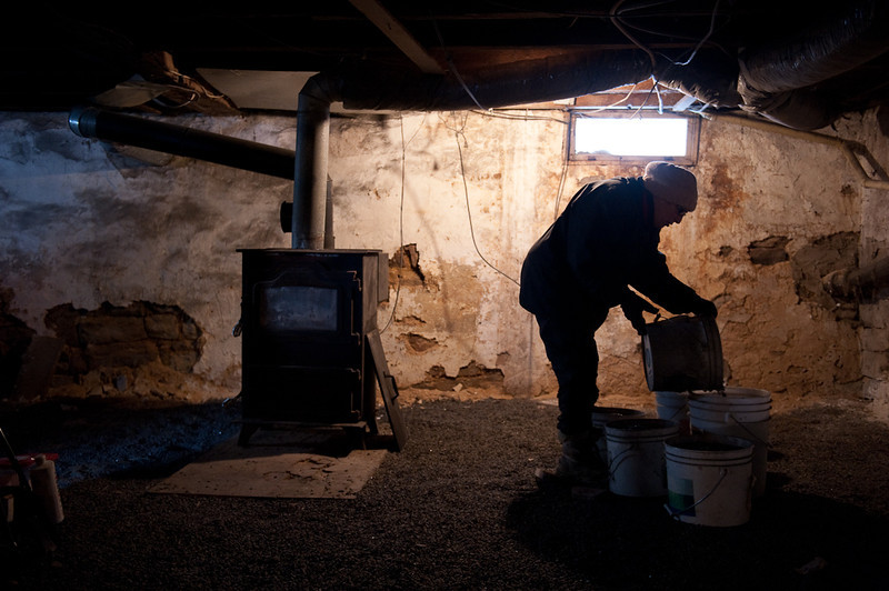 Barb Rossman dumps coal into reserve buckets in the basement of her house on Jan 29, 2011. Her house, built in the 1800s, is heated entirely by two coal stoves. The one at left, however, is giving her trouble this morning. Her house's inside temperature would drop into the 50s overnight as a result, but her son, busy with farm work, hasn't had time to fix it yet.