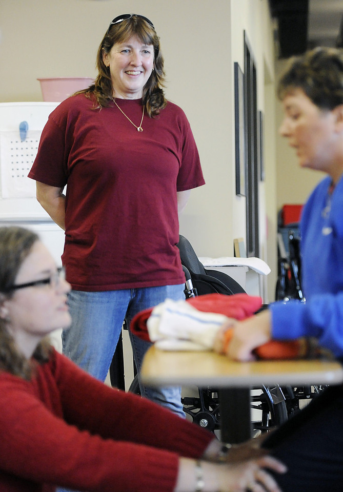Dana Beck, center, of Millcreek Township, watches as occupational therapist Michelle Mioduszewski, bottom left, of Erie, works with Beck's partner Mary Ann Schmeisser, right, also of Millcreek Township, an occupational therapy session in Erie on Dec. 6. Schmeisser is an Erie police officer who was severely injured on the job when she was hit by a vehicle while investigating a police call on the night of Dec. 14, 2011. Since the accident, Schmeisser and Beck are working together to stay upbeat and positive as Schmeisser heals. ANDY COLWELL/