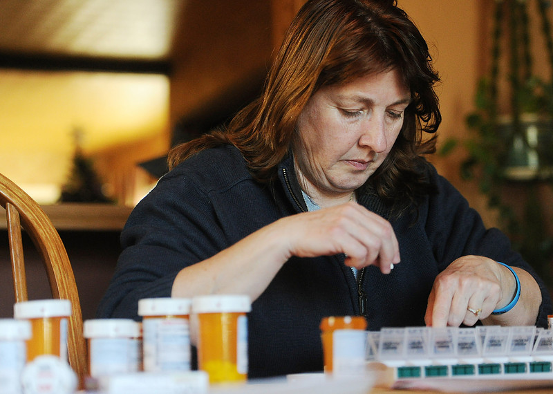 Dana Beck sorts medication for her partner Mary Ann Schmeisser at their Millcreek Township home on Dec. 12. Schmeisser is an Erie police officer and was severely injured on the job when she was hit by a vehicle while investigating a police call on the night of Dec. 14, 2011. She needs more than a dozen medications a day to treat her traumatic brain injuries. Since the accident, Schmeisser and Beck are working together to stay upbeat and positive as Schmeisser heals. ANDY COLWELL/