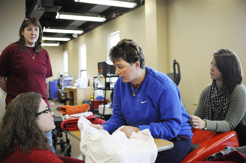 Mary Ann Schmeisser, at center, works on occupational therapy lessons with Michelle Mioduszewski, bottom left, of Erie, and Vanessa McGraw, right, of Youngsville, as Schmeisser's partner Dana Beck watches at back left in Erie on Dec. 6. Schmeisser is an Erie police officer who was severely injured on the job when she was hit by a vehicle while investigating a police call on the night of Dec. 14, 2011. Since the accident, Schmeisser and Beck are working together to stay positive and upbeat as Schmeisser heals. ANDY COLWELL/