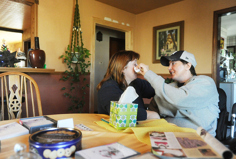 As Dana Beck, left, cries, her partner Mary Ann Schmeisser wipes away the tears as the two share an emotional moment at their Millcreek Township home on Dec. 12. Schmeisser is an Erie police officer and was severely injured on the job when she was hit by a vehicle while investigating a police call on the night of Dec. 14, 2011. Since the accident, Schmeisser and Beck are working together to stay upbeat and positive as Schmeisser heals. ANDY COLWELL/