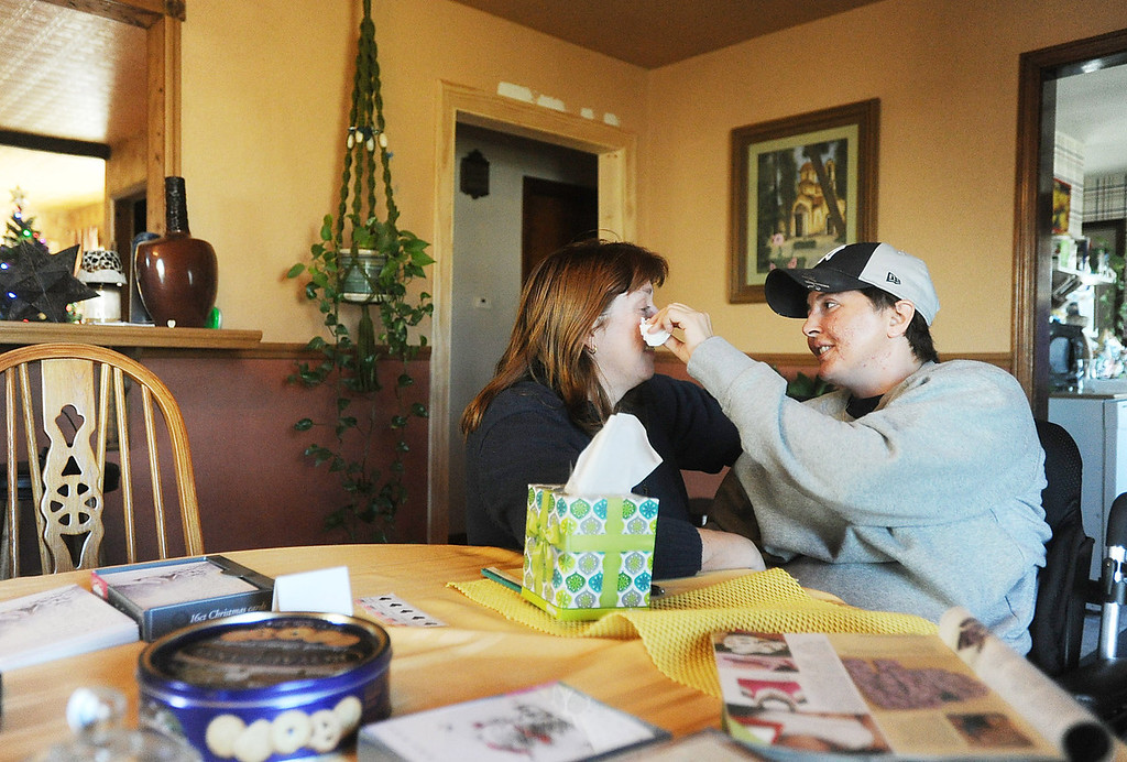 As Dana Beck, left, cries, her partner Mary Ann Schmeisser wipes away the tears as the two share an emotional moment at their Millcreek Townshiphome on Dec. 12. Schmeisser is an Erie police officer and was severely injured on the job when she was hit by a vehicle while investigating a police call on the night of Dec. 14, 2011. Since the accident, Schmeisser and Beck are working together to stay upbeat and positive as Schmeisser heals. ANDY COLWELL/