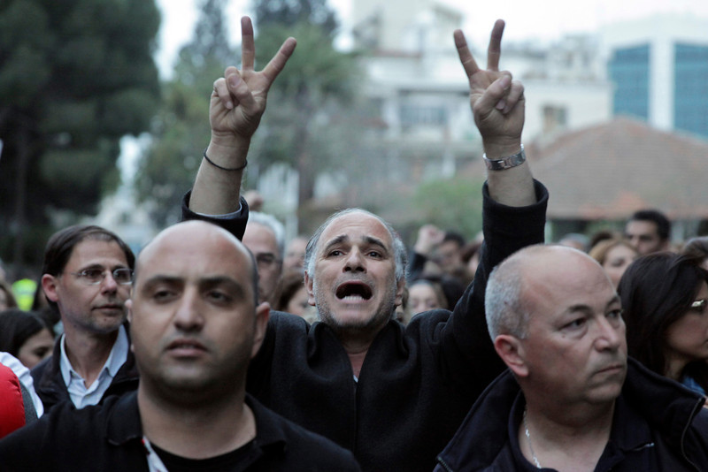 A Cypriot flashes the sign of victory during a protest outside the Parliament on March 21, 2013 in Nicosia.