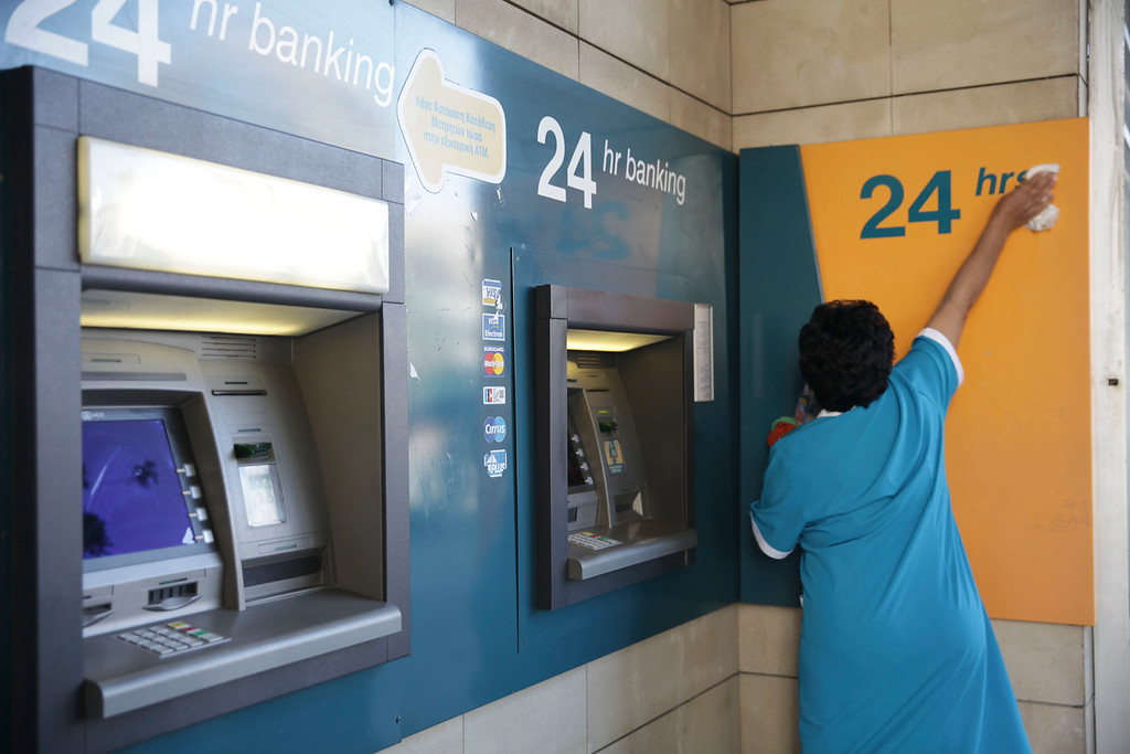 CYPRUS, Nicosia : A woman cleans cash points in the old part of the Cypriot capital, Nicosia, on March 28, 2013