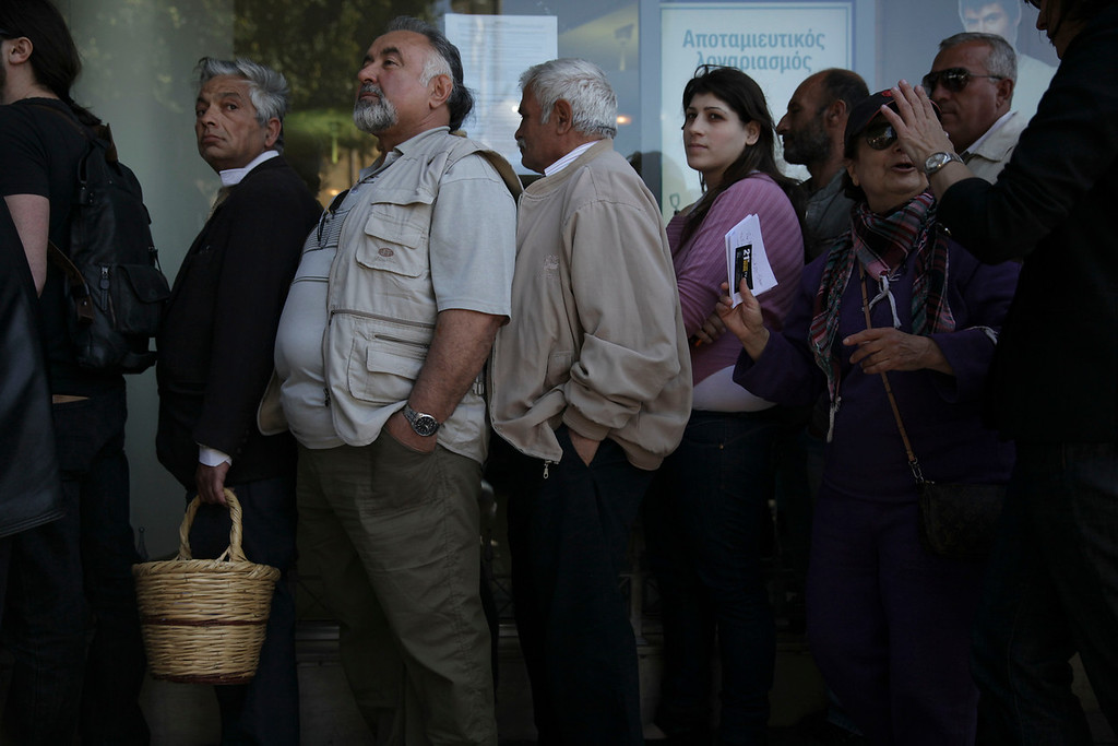 CYPRUS, Nicosia : People queue up outside a Laiki bank branch in the Cypriot capital, Nicosia, on March 28, 2013, as they wait for the bank to open after an unprecedented 12-day lockdown. Queues of dozens of people formed before the doors swung open at 12:00pm (1000 GMT) for the first time since March 16, and there were tensions as a few branches opened late, with customers banging on the doors.