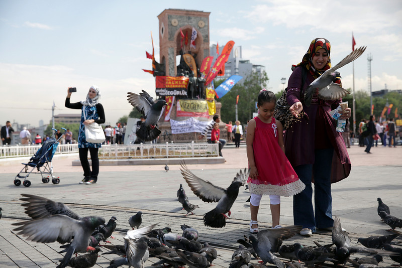 June 05,2013- Istanbul,Turkey:  A woman feeds pigeons in Taksim square .The protests began initially over the fate of Taksim Gezi Parhek, one of the last significant green spaces in the center of the city.