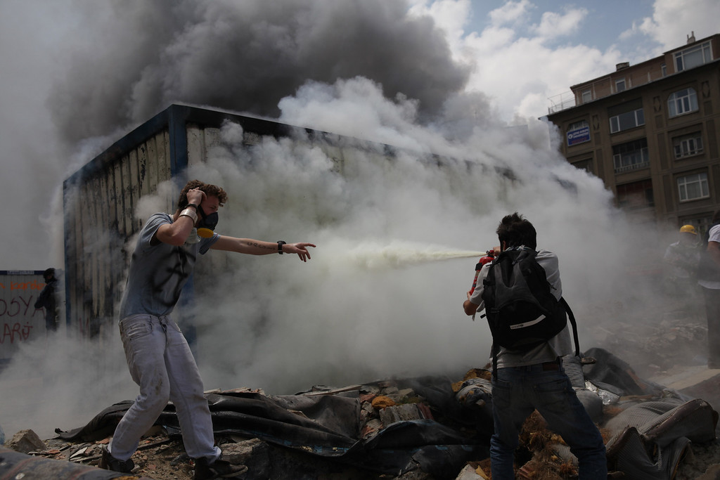 June 04,2013- Istanbul,Turkey:A Protestor try to put down a fire in a container used for construction workers on June 4, 2013 in Istanbul, Turkey.The protests began initially over the fate of Taksim Gezi Park, one of the last significant green spaces in the center of the city