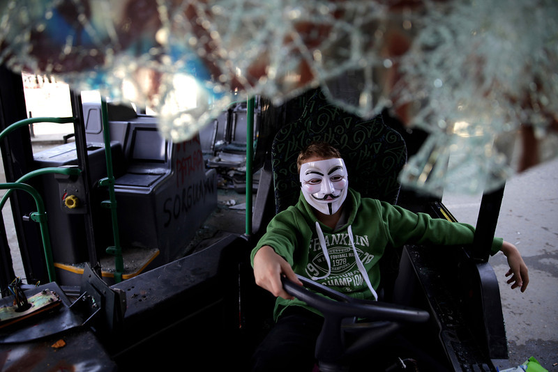 June 05,2013- Istanbul,Turkey:  A boy wearing a mask sits inside the damaged bus in Taksim Gezi park.The protests began initially over the fate of Taksim Gezi Parhek, one of the last significant green spaces in the center of the city