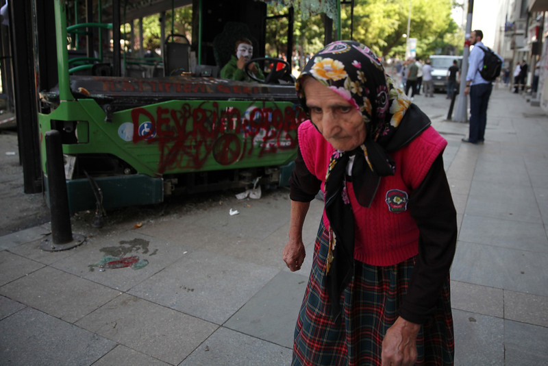 June 05,2013- Istanbul,Turkey:  A woman passes by a damaged bus in Taksim Gezi park.The protests began initially over the fate of Taksim Gezi Parhek, one of the last significant green spaces in the center of the city