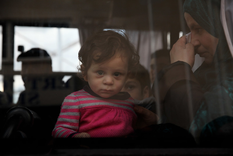 A  Syrian refugee who was rescued off the coast of Cyprus sits in a bus at the port in Kerynia  on November 23, 2014 as they are transported to back to the posrt to travel back to Turkey