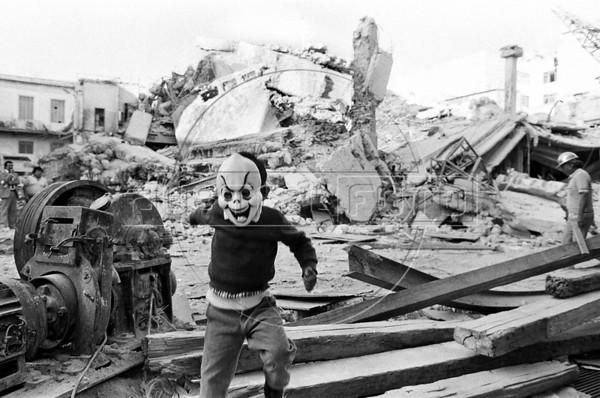 Dias despues del terremoto del 19 de setiembre, 1985 que devasto la ciudad de Mexico, entre los escombros, los rescatistas tratando de salvar victimas atrapadas en las ruinas, el olor a cadaver, aparece como una vision un nino enmascarado, se detiene un minuto, hace un gesto y sigue corriendo, Mexico DF, Mexico, Setiembre 20, 1985.  (Austral Foto/Renzo Gostoli)