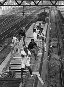 "Illegal train passengers ""surf"" on one of the government-owned metropolitan commuter trains in Rio de Janeiro in this 1988 photograph. Hundreds of people used to take the train without paying before the trains were privatized, in what was considered part sport, and part dare and part commute. The Supervia company took control of Rio commuter railways in 1998, implementing modernization measures, such as the banning of train surfing, line and station improvements and new rail cars. (Austral Foto/Renzo Gostoli)"