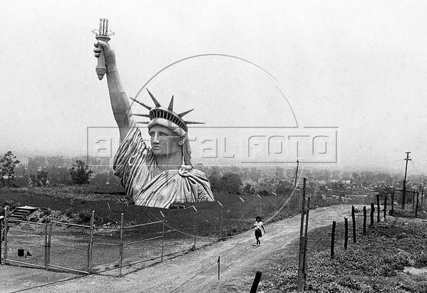 Una nina pasa frente a una replica de la estatua de la libertad, Iztapalapa, Mexico DF, Mexico, Junio, 1985. La estatua fue usada en la filmacion de una pelicula estadounidense. (Austral Foto/Renzo Gostoli)
