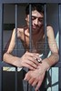 "Francisco Valladares, known as ""Demonio,"" a member of the Mara Salvatrucha gang, hangs his hands through the bars of a jail cell in San Salvador, El Salvador, Nov. 29, 1995. He drove a friend's car into food stand in downtown San Salvador while driving dunk. Virtually unknown before the end of the civil war four years ago, gangs are an explosive phenomenon sweeping El Salvador, conveniently filling the niche of violence left when the war ended.(AustralFoto/Douglas Engle)"