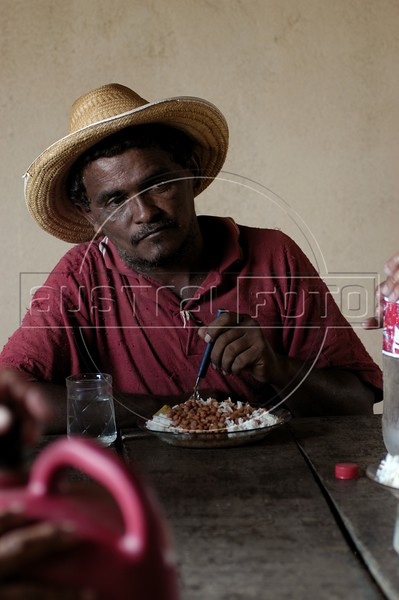 A worker has lunch on the Peruano ranch south of Maraba, in Brazil's Amazonian state of Para, Oct. 5, 2004. The Brazilian Federal government expropriated another ranch owned by the Mutran family, the Castanhal Cabaceiras ranch, in October 2004, to use for agrarian reform. According to the Labor Ministry, the owner used slave labor, whose officials found it on four separate auditory raids. This is the first time land has been confiscated due to slave labor. The owner is also accused of cutting down the rainforest and annexing land illegally through the use of false documents. The ranch is 9.7 thousand hectares, which will be divided between 250 families.(Australfoto/Douglas Engle)