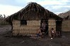Gregorio Pereira sits in front of his thatched hut with family members at a camp of the Landless Workers Movement (MST) dot the landscape of the Peruano ranch, owned by Evandro Mutran, south of Maraba, in Brazil's Amazonian state of Para, Oct. 5, 2004. The workers, which squat on land to pressure the federal government, demand expropriation of the land due to several irregularities. The Brazilian Federal government expropriated another ranch owned by the Mutran family, the Castanhal Cabaceiras ranch, in October 2004, to use for agrarian reform. According to the Labor Ministry, the owner used slave labor, whose officials found it on four separate auditory raids. This is the first time land has been confiscated due to slave labor. The Mutrans are also accused of cutting down the rainforest and annexing land illegally through the use of false documents. The expropriated ranch is 9.7 thousand hectares, which will be divided between 250 families.(Australfoto/Douglas Engle)