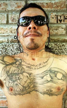"""El Chino"" proudly shows off his tattoos in Apopa, El Salvador. Gangs have proliferated since the end of the 12-year civil war in 1992, when some one million refugees who left for the U.S. during (and before) the war began returning. They bring with them customs and values, good and bad, learned there. Gang Grafitti is everywhere, and after Coca-Cola, gangs appear to be the most visible import from the United States.(AustralFoto/Douglas Engle)"