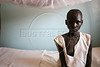 Ayan Mayan, 13 sits on her bed at a hospital run by a Catholic mission in Mapuordit, southern Sudan, Nov. 23, 2005. Mayan who lost her child, is slowly recovering from the operation she had to remove it. Although the peace accord signed in Jan. 2005 ended the war between the Islamic north and non-Muslim south, years of civil war have taken their toll. The presence of any government or infrastructure is minimal, if at all. The missions and other NGOs in the region provide vital basic services for the population, which is slowly growing around the relief and aid centers. While the war is over, the Catholic church sees that the battle with the Islamic Sudanese government for the hearts and minds of the people of south Sudan is just beginning. After a six-year transitionary period, the south Sudanese will vote in a referendum on independence.(Australfoto/Douglas Engle)
