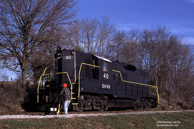 """Here is a little story from a couple of years ago—a day at work on the Shenandoah Valley Railroad. We left Staunton that morning with a crew of three: the engineer, a trainee engineer, and me, as conductor. By chance, Mike Derrick, publisher of <a href=""""http://www.shortlinesusa.com"""">Shortlines USA</a>, was visiting that day to take photos for his website. We had, as I recall, 10 cars loaded with soy meal headed for Pleasant Valley to be transferred to the Norfolk Southern.  ---- Here is your author throwing the North Weyers Cave siding switch. ----"""