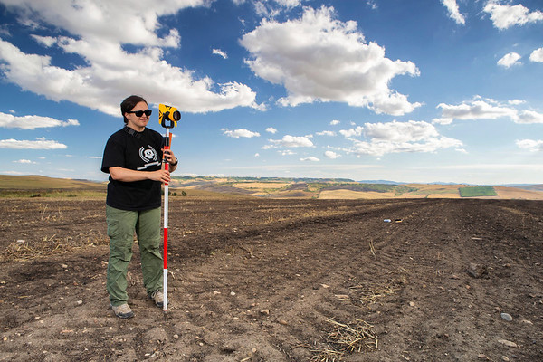 An archaeologist holds a prism while mapping out trenches at the Vagnari cemetery.
