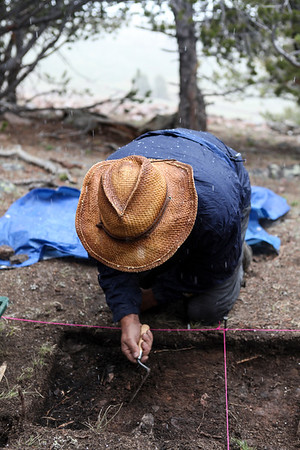 An archaeologist excavates a lodge in High Rise Village during a late summer snowstorm.