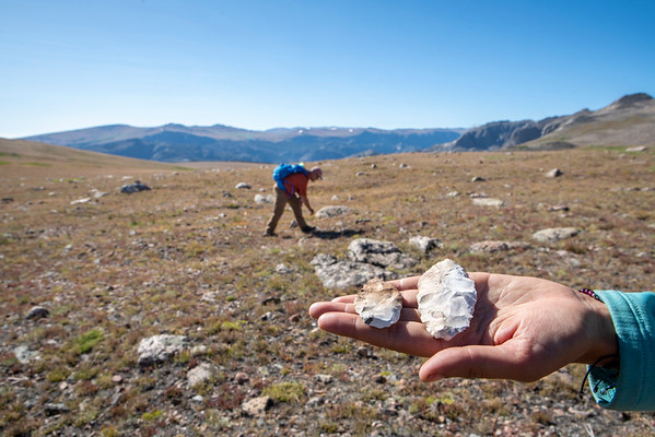 Archaeologist Rebecca Sgouros holds a pair of white chert bifaces that were found high above treeline.