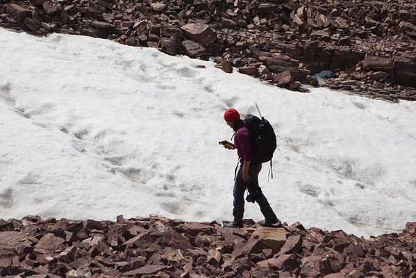 An archaeologist walks around an alpine icepatch with a gps to map its size.