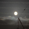 Perigee full moon behind tower crane