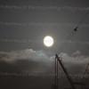 Perigee full moon behind tower crane