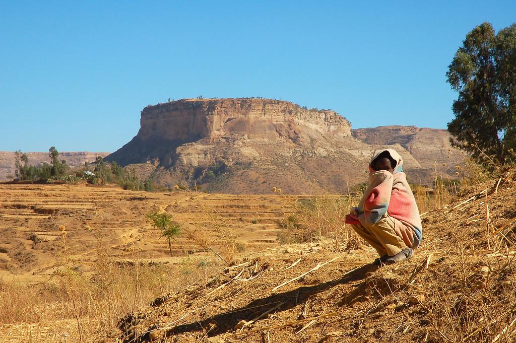 """C'était une belle journée et le voyage, à travers l'un des paysages les plus spectaculaires au monde, ne le fut pas moins. Chez moi, quelques mois plus tôt, j'avais lu un article dans un journal à propos d'un """"monastère en haut d'une falaise"""".  J'ai su alors que je voulais aller en Ethiopie. Depuis l'intersection avec la route principale, il faut parcourir 11 kilomètres de piste chaotique pour arriver jusqu'au bas de la montagne, et cette piste n'est praticable qu'en 4x4.Le véhicule avait bien du mal et finit par abandonner après quelques kilomètres et j'ai dû marcher. Debre Damo est unique et inoubliable. Il y a un obstacle de taille à franchir: le seul moyen d'accéder au monastère est d'escalader une falaise escarpée de 24 mètres de haut. Parfaitement polie par tous les moines l'ayant escaladée au cours des quatorze siècles de son existence, la falaise me paraissait de plus en plus infranchissable à mesure que j'avançais. Un moine abaissa une corde de sécurité que je passai autour de ma taille. Il en fit alors descendre une seconde, une corde de cuir plus épaisse et effilochée, celle qui relie les moines au monde extérieur. J'agrippai la corde de mes mains, et, pieds nus, je grimpai. Ce fut presque une ascension spirituelle, un sentiment puissant m'a envahi durant toute la montée et un pouvoir que je n'avais jamais ressenti auparavant me donna la force de me hisser jusqu'en haut. Je réussis l'ascension, atteignis le haut et, jetant un coup d'oeil vers le bas, n'en revins pas de l'avoir fait. <br /> Le monastère est un ensemble de maisons de pierres et de plusieurs petites églises réparties sur les flancs arides de la montagne. Environ 120 moines y vivent, avec leurs protégés et leur cheptel. Les gens des environs leur donnent de la nourriture et autre mais la communauté monastique s'auto-suffit littéralement. Elle a ses propres réservoirs d'eau - des cavernes spectaculaires creusées en profondeur sous la surface des falaises il y a des siècles de ça. Peu d'indices"""