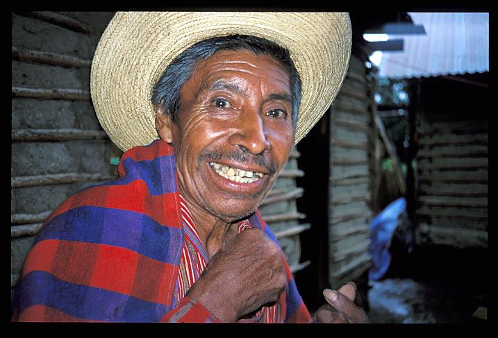 """Guatemala<br /> """"Atitlan""""<br /> Paul Théroux décrit le Guatemala comme un lieu laid, brutal et insipide, et cependant, pour moi, c'est le pays d'où l'Arc-en-Ciel tient ses couleurs. J'ai rencontré ce type à Santiago, sur les rives du Lac Atitlan, un cratère de volcan entouré par des pics volcaniques. D'une beauté si irréelle que les Indiens pensent que c'est le nombril de la Terre. Quand on voyage ici, c'est par les """"bus à poulets"""" qui parcourent le pays en cahotant. Le bus qui nous emmenait au lac était si bondé que je m'assis sur un sac de maïs à même le sol. A ma droite, une dame allaitait son bébé, et à ma gauche se tenait un vieil homme avec un carton sur les genoux qui contenait quatre coqs. La femme devant moi portait son enfant attaché dans un châle sur son dos, et elle était cramponnée à un morceau de tissu enveloppant deux porcelets hurlants. Il y avait là tant d'humains, d'animaux et de volailles serrés les uns contre les autres dans cet ancien car scolaire que l'odeur était celle d'un zoo. Et il me restait encore trois heures de ce """"théâtre vivant"""" avant de parvenir à destination. Génial."""