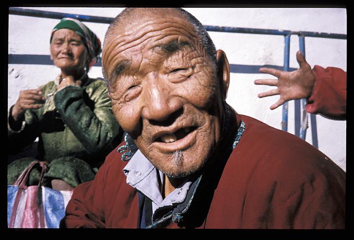 """Mongolie<br /> """"Conversation de trottoir""""<br /> Je suis arrivé de Chine en Mongolie par le Trans-Sibérien express. Les Mongoliens, dans leur capitale, semblaient méfiants à l'égard des étrangers. Je suis arrivé dans leur pays sans habits chauds, et, l'hiver s'installant, je m'achetai un """"deal"""", c'est-à-dire un long manteau qui ressemble à une lourde robe de chambre en laine. Me voyant vêtu du vêtement national, cet homme m'invita à le rejoindre pour bavarder un instant sur le trottoir. Quand vous avez toute la journée devant vous, cela n'a pas d'importance qu'il vous faille deux heures pour expliquer que vous venez de loin et que vous êtes heureux d'être avec eux, dans leur pays. Il me retint pour partager avec lui son dîner sous sa tente. Et la main dans la photo, me direz-vous? Eh, bien, elle aurait pu être effacée, mais elle faisait partie de cet instant..."""