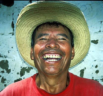 """"""" Rook Rook """" Guatemala<br /> Un jour, j'ai pris un bateau pour me rendre au pied d'un volcan, dans un petit village au bord d'un lac. En partant de la jetée, alors que je m'approchais du village, ce type m'a demandé de l'argent. J'avais une sucette dans ma poche arrière, et je la lui tendis. Quand je lui ai demandé si je pouvais le prendre en photo, il a regardé la sucette et m'a fait ce sourire. Je promis de lui envoyer un double de la photo, mais perdis son adresse. Un an plus tard, je suis retourné au Guatemala, emportant avec moi le double de la photo. Avec l'aide d'un garçon du village, j'ai trouvé sa maison. Mais à ma grande déception, il n'était pas là. Je laissai la photo à sa femme, qui était enchantée. En partant, j'ai remarqué Rook Rook, assis à regarder les bateaux aller et venir. Je savais à présent l'espagnol, et j'essayai de lui faire savoir que j'avais laissé une photo chez lui. Je ne comprenais pas pourquoi il ne me comprenait pas jusqu'à ce qu'une femme, qui écoutait la conversation, me dise qu'il était sourd et muet. Il savait lire sur les lèvres, mais seulement sa langue maternelle Indienne, et pas l'espagnol. Avec l'aide de cette femme, je me suis débrouillé pour lui transmettre le message selon lequel j'avais laissé à sa femme une photo. Je suis retourne au Guatemala en 2004, pour apprendre que Rook-Rook etait mort quelques mois auparavant dans un accident survenu dans  les docks."""