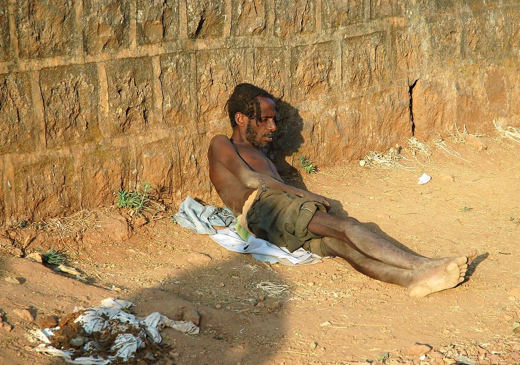 """Addis Ababa<br /> J'étais assis à la terrasse d'un café, une tasse devant moi. De l'autre côté de la route, il devait bien y avoir une centaine de personnes, adossées ou endormies au pied d'un mur qui bordait toute la route: des mendiants. Certains difformes, d'autres nus, d'autres encore malades (pour beaucoup, du Sida), certains avec un membre brisé ou amputé, d'autres qu'on aurait peur de toucher, mais pour tous, la vie s'écoulait ici même, chaque jour. Ils mendiaient tous, et la réaction première, une fois le choc passé, est peut-être de vous dire que dans un sens tout cela est de leur faute. C'est la solution facile, ça vous permet de marcher devant eux et de ne rien faire, de donner une pièce ici ou là à ceux qui réveillent votre conscience. Et cependant, quand ils réclament de l'argent, si vous leur donnez à la place un bout de pain, on vous l'arrachera des mains et il sera dévoré comme jamais je n'ai vu ça. La pauvreté, ce n'est pas le fait de """"ne rien avoir"""", c'est, comme me l'a dit l'homme rencontré au café, le fait """"d'être quelqu'un dont le potentiel dans cette vie ne se réalisera jamais"""". Aucun espoir, et je n'ai pas la moindre idée de ce que peut être une vie sans espoir, aucun d'entre nous ne le sait, mais l'avoir vue jour après jour, à travers ces mains qui se tendent non pas vers l'espoir mais vers la nourriture, cela m'a serré le coeur."""