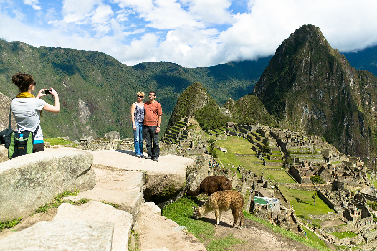A couple has their photo taken with Huanac Picchu in the background.