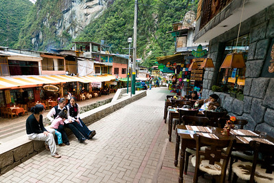 """Waitresses wait for tourists outside a restaurant in Aguas Calientes. Restaurants will do just about anything to get tourists inside. It's impossible to walk down the street without hearing """"Amigo, come inside. Eat lunch. Pizza, pisco sour...good price!"""""""