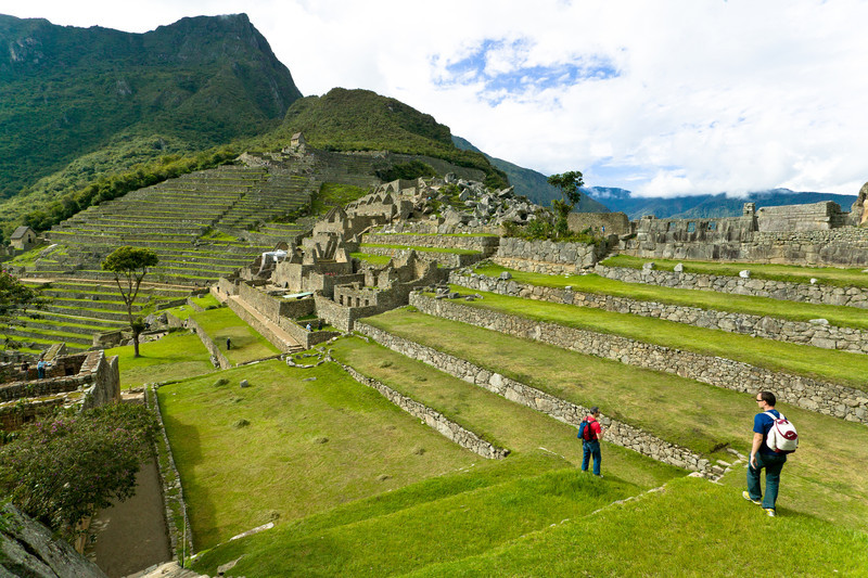Two Spanish tourists explore Machu Picchu's Central Plaza. Incan terraces were used to grow a variety of crops like potatoes and maize to feed the 700 permanent inhabitants. The purpose of Machu Picchu, long thought to be a place of human sacrifice and an Incan hideout, is now thought by most experts to have been used as a royal retreat and place of ceremony.