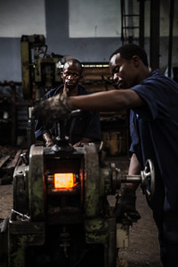 Workers bend steel to make leaf springs in Nairobi.