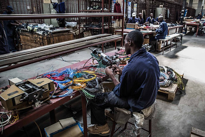 A worker assembles wiring in an automobile wiring factory in Nairobi, Kenya.