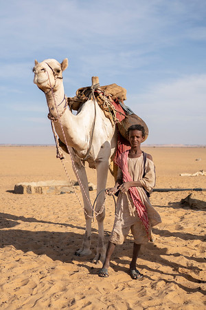 A Bishari nomad and his camel at a watering hole in the Bayuda Desert