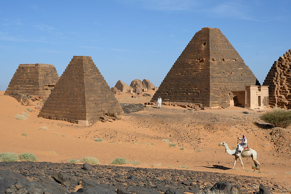 A Nubian man rides a camel near pyramid tombs in the southern necropolis of Meroë.   This cemetery, used between 350BC to 300AD, contains over fifty pyramids and served as the necropolis for the capital city. The pyramids are a UNESCO World Heritage site.  The Kingdom of Kush flourished in modern day Nubia between 2000 BC - 350 AD, successfully invading Egypt during the 25th Dynasty and establishing a line of influential kings and queens who ruled along the Nile.