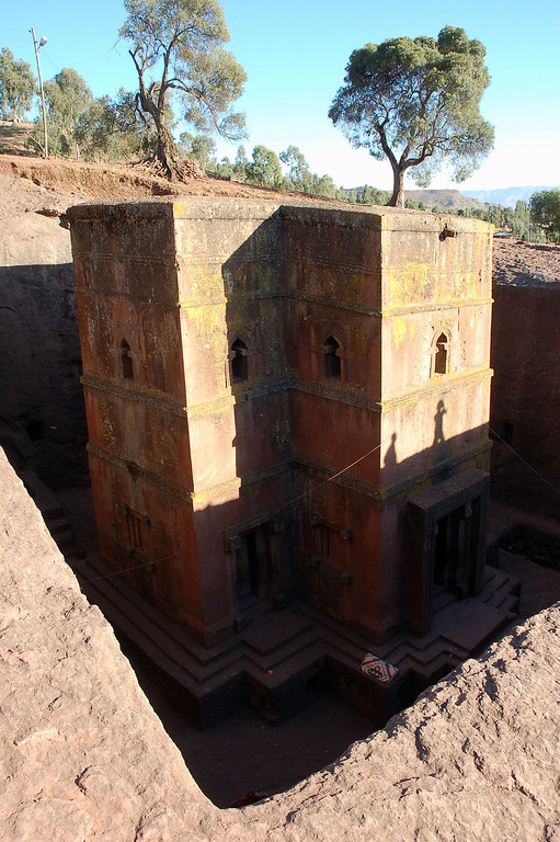 Lalibela<br /> <br /> There is a small town in the middle of the Ethiopian highlands. It's surrounded by a rocky arid area. Yet here they say and I include myself among them, you will find the 8th wonder of the world. The town is known as Lalibela, after a legendary ruler, who according to legend  was, while in Jerusalem, taken to heaven by an angel, where God gave him a vision of churches such as no one had ever seen before and ordered him to build them. It is said that angels came at night and helped with the construction.<br /> Looking from the entrance on top of the mount, the first impression of the church is its giant cross-shaped roof. A few steps further, the twelve-meter-high, cross-shaped church can be seen standing tall and upright in the square hole below.<br /> <br /> Try, if you can, to imagine a cathedral carved into a pit of solid rock? How would you make it? Shape the exterior of the building. Make some doors and windows. Then carve into the rock to form the inside the building to making, rooms, an alter, passage ways. Using only hand tools. An awesome feat, yet here in Lalibela there are eleven of them