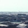 The village of Teguidda-n-Tessoumt beside the salt pans. A crane or excavator jib on the distant horizon.