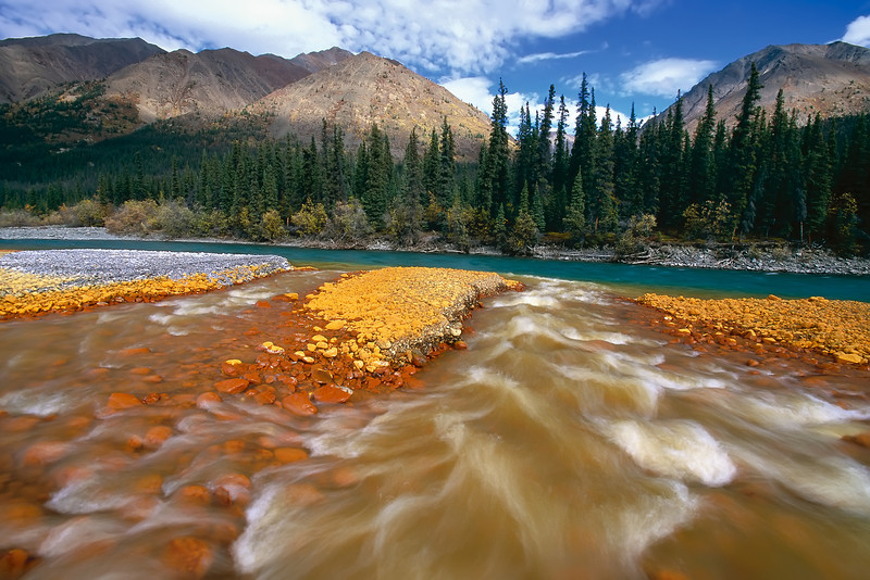 An orange creek flows into the blue waters of the Snake River, with the MacKenzie Mountains in the background. The slow motion photo blurs the moving water giving a sense of movement. Yukon, North, Canada