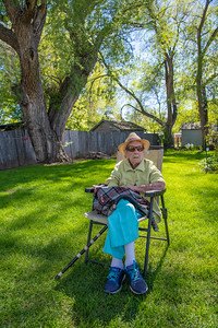Helen Aragon, age 103, sits in her backyard in the Spanish Colony neighborhood of Fort Collins, Colo. She has lived in her home for more than 50 years, where she cared for her family after her husband's early death. Chickens and turkeys once roamed this lot. May 2019.